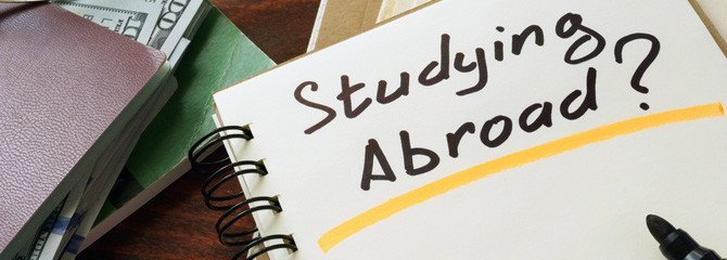 Notepad with Studying Abroad? on the wooden table.